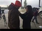Crew member Kendall Haven is helped with a microphone by KHQ TV reporter Katie Chen.