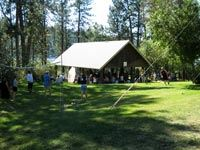 A large group of people gathered inside a picnic shelter.