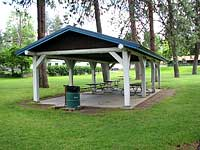 A white wooden picnic shelter with blue roof.
