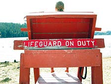 A sign attached to a chair which reads, &#34Lifeguard on duty.&#34