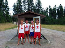 Four young men in lifeguard shirts standing in front of a shed.