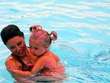 A woman in a pool holding a small girl.