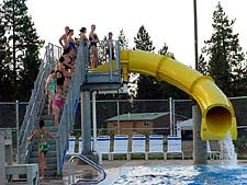 A group of young people climbing the steps of a waterslide.