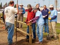 A group of men installing a wooden fence.