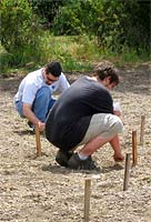 Two men planting seeds in the ground.