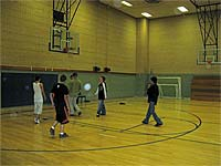 A group of youths playing basketball in a gymnasium.