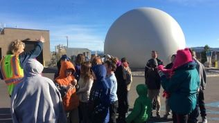 Tour group in front of methane storage ball.