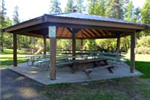 A wooden shelter with several picnic tables inside.
