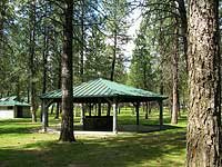 A small picnic shelter with a green roof.