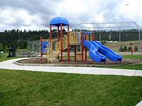 A colorful playground next to a paved path.