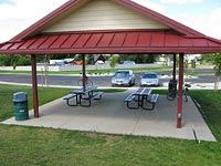 A red picnic shelter with picnic tables within.