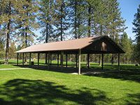 Wooden shelter in a large grassy area.