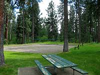 Image of a picnic table in a clearing of trees.