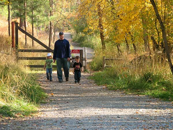 A man walking with two small children on a trail.